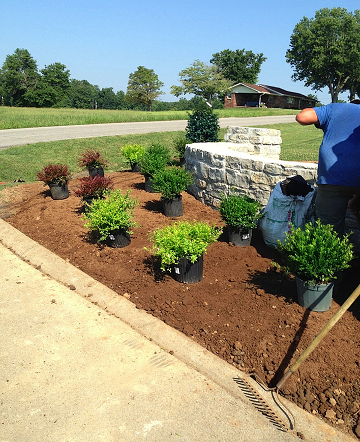 Laying out landscaping around the Meadows' stone wall entrance